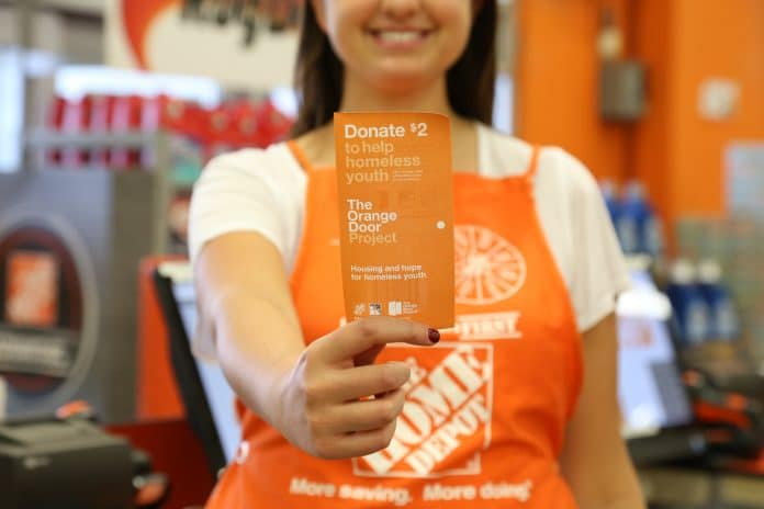 A Home Depot employee holding an Orange Door (being sold to support homeless youth).